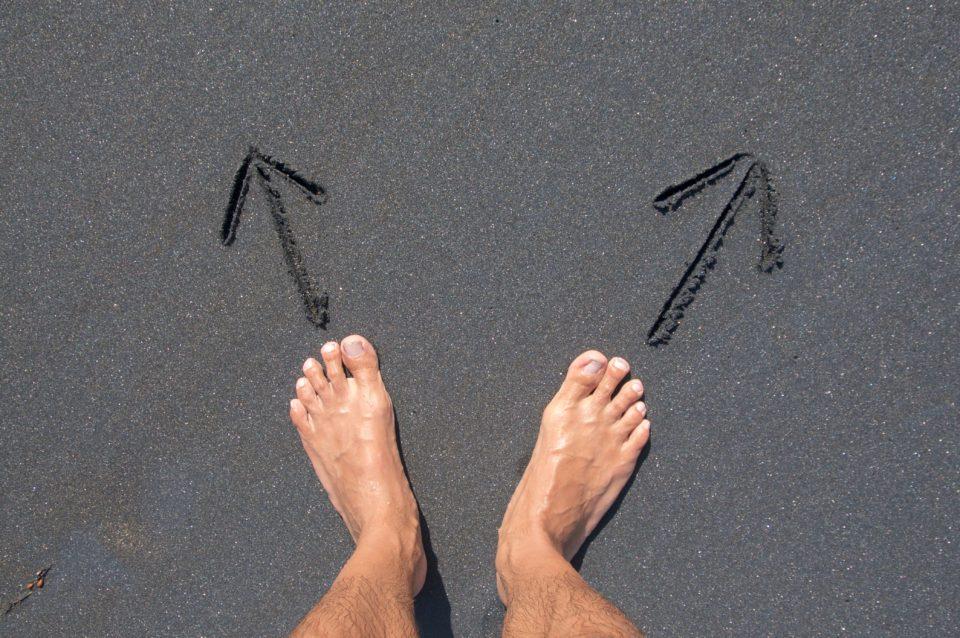 Dos pies desnudos sobre la arena. Delante de cada pie hay una flecha que indica como dos caminos distintos, dos direcciones hacia las que esta persona se podría dirigir.