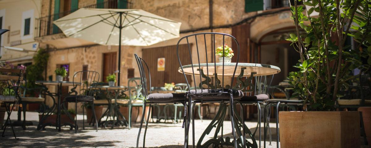 Una terraza de Palma de Mallorca en una soleada tarde de verano. Se ve una sombrilla y algunas mesas y sillas de la terraza del bar.