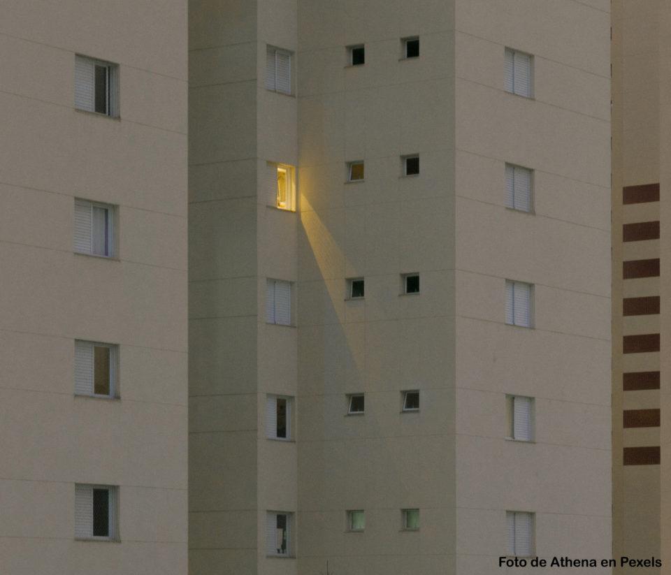 Vista de la fachada de un gran edificio de pisos en el que se ven numerosas ventanas, pero solo una con la luz encendida.