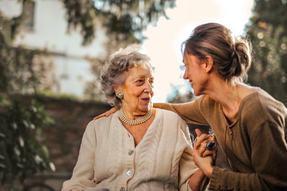 Una señora mayor junto a su hija que la cuida